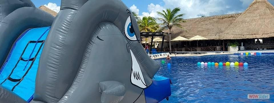 Tobogan inflable con forma de tiburón junto a una gran alberca