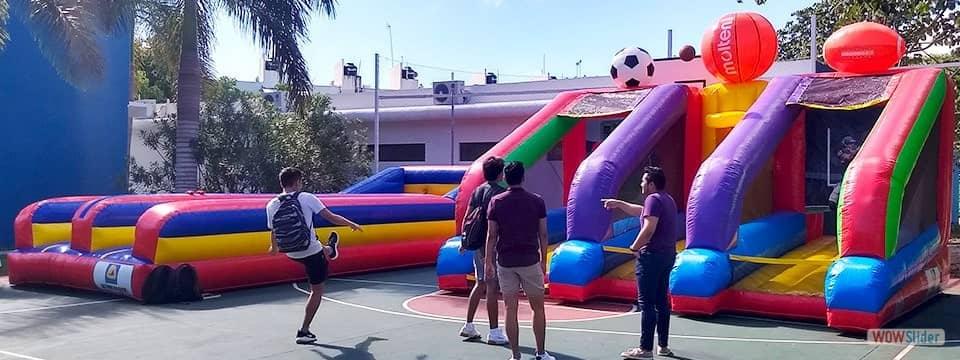Estudiantes interactuando con inflables deportivos en la cancha de basquetball de su colegio.