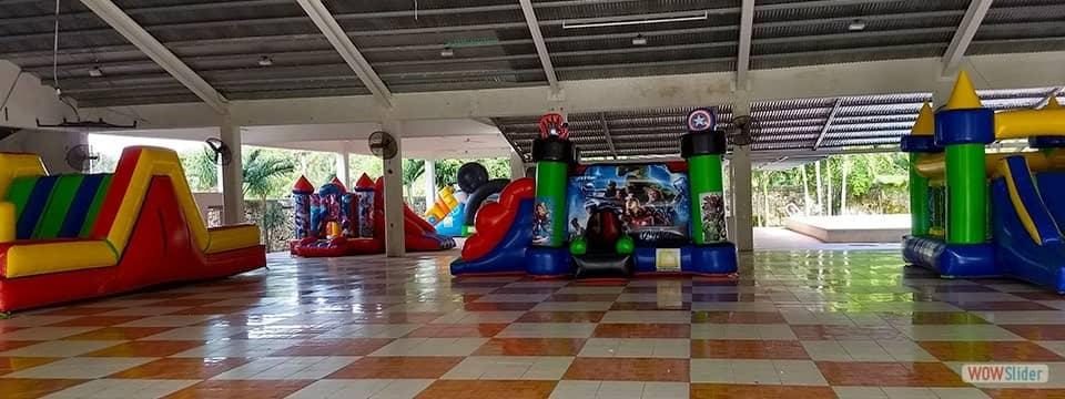 Cinco brincolines inflables distribuidos en un salón de eventos.